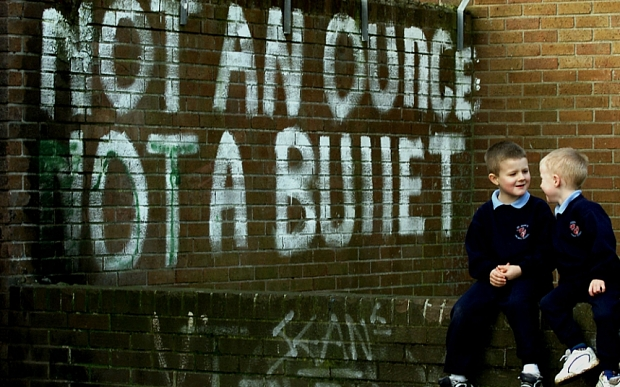IRA...Catholic school children play under the shadow of IRA graffiti in the Republican area of Twinbrook in West Belfast, Northern Ireland, Friday, February 4, 2000. The writing refers to the current decommissioning issue which has put the Northern Ireland peace process in trouble due to the failure of the IRA to start decommissioning its weapons. (AP Photo/Peter Morrison)