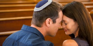 Man in yarmulke praying with girlfriend